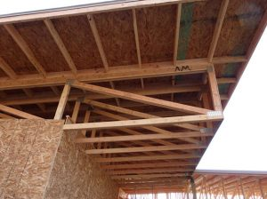 The deep truss provides more than 2 feet of space for insulation. The overhang shades the building's south wall.