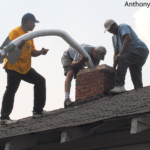 A crew installs a metal chimney liner into a masonry chimney.